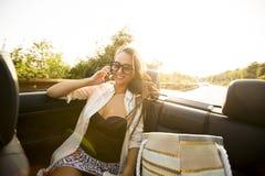 Kvinnan använder mobiltelefonen och att placera i cabriolet på sommardagen Arkivfoton
