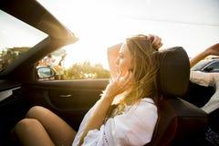 Kvinnan använder mobiltelefonen och att placera i cabriolet på sommardagen Arkivbilder