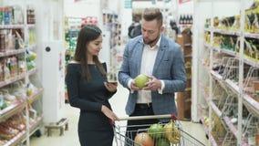 Kvinnan använder smartphonen till kontrolllistan av produkter, och mannen väljer frukter och luktar den i supermarket stock video
