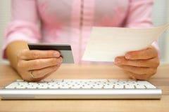 Kvinnan använder debitering eller kreditkorten för att betala direktanslutet räkningarna och Arkivfoton