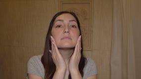 Kvinnan applicerar kräm på hennes framsida applicera genomskinlig fernissa för omsorgshud stock video