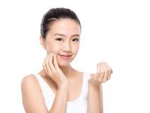 Kvinnan applicerar skincare på framsida Royaltyfri Fotografi