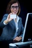 Kvinnan arbetar på datoren och uppvisning av ett kort Arkivfoto