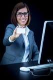 Kvinnan arbetar på datoren och uppvisning av ett kort Royaltyfria Foton