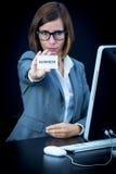 Kvinnan arbetar på datoren och uppvisning av ett kort med text Royaltyfria Bilder