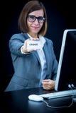 Kvinnan arbetar på datoren och uppvisning av ett kort med text Royaltyfri Bild