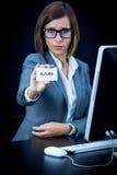 Kvinnan arbetar på datoren och uppvisning av ett kort med text Arkivfoton