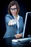 Kvinnan arbetar på datoren och uppvisning av ett kort med text Royaltyfri Foto