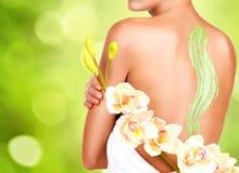 Kvinnan att bry sig om hud av kroppen som använder skönhetsmedlet, skurar på baksidan Royaltyfri Bild