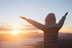 Kvinnan att lyfta deras armar upp himlen, tackar guden, morgonsoluppgångbakgrunden, Christian Religion begreppsbakgrund royaltyfri bild