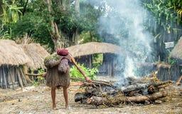 Kvinnan av den Dani Dugum stammen lagar mat mat och använder en jordugnsmetod av matlagningsvinet Royaltyfria Foton