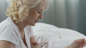 Kvinnan av den höga åldern som ber på hennes säng, ögon stängde sig och att le, tacksamhet till guden arkivfilmer