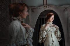 Kvinnan av en spegel gör framme toaletten Royaltyfri Fotografi