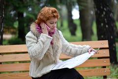 Kvinnan av genomsnittliga år kallar enligt meddelandet i tidningen härligt dimensionellt jobb tre för illustration 3d mycket Royaltyfria Foton