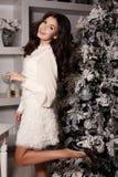 Kvinnan bär den eleganta klänningen som poserar bredvid den dekorerade julgranen Arkivfoton