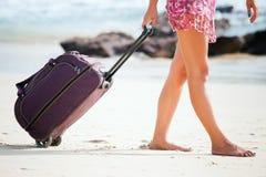 Kvinnan bär ditt bagage på den sandiga stranden Arkivbilder