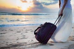 Kvinnan bär ditt bagage på den sandiga stranden Royaltyfri Foto