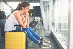 Kvinnan bär ditt bagage på flygplatsterminalen royaltyfri foto