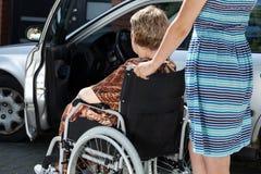 Kvinnan bär en gammal dam i en rullstol Royaltyfri Bild