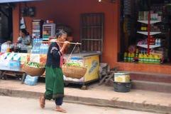 Kvinnan bär ett ok på den Luang Prabang staden Loa Fotografering för Bildbyråer