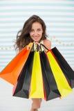 Kvinnan bär gjord randig bakgrund för gruppshoppingpåsar Slutligen köpt favorit- märke Spetsar shoppar försäljningar Tillfredsstä royaltyfri foto