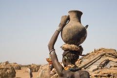 Kvinnan bär på hennes huvud en behållare med vatten, Etiopien Arkivbilder