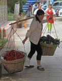 Kvinnan bär två backets med körsbär och druvor royaltyfria foton