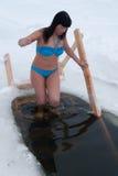 Kvinnan badar i hålet i vintern Arkivbild