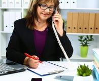Kvinnan bak skrivbordet i kontoret Royaltyfri Fotografi