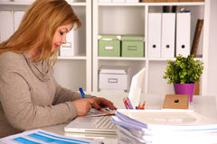 Kvinnan bak skrivbordet i kontoret arkivfoton