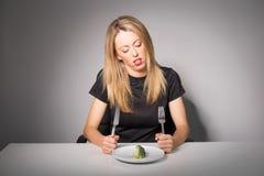 Kvinnan bantar på äta broccoli Fotografering för Bildbyråer
