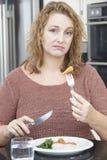 Kvinnan bantar på Fed Up With Eating Healthy mål Arkivfoto