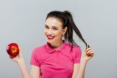 Kvinnan bantar på med ett äpple i handen mot grå bakgrund Fotografering för Bildbyråer