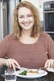 Kvinnan bantar på äta sunt mål i kök Arkivfoto