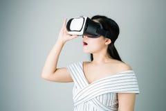 Kvinnan bar en virtuell verklighethörlurar med mikrofon, som simulerar, verkligheten och såg royaltyfria bilder