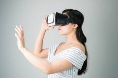 Kvinnan bar en virtuell verklighethörlurar med mikrofon, som simulerar, verkligheten, och sett upp till se vad virtuella verkligh fotografering för bildbyråer