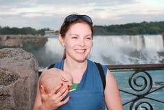 Kvinnan behandla som ett barn och vattenfallet Arkivbild