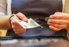 Kvinnan betalar kontant med eurosedlar Fotografering för Bildbyråer
