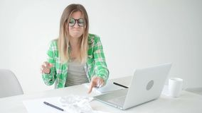 Kvinnan betraktar beloppet av kostnader för köp och betalning av krediteringar, genom att skriva in information in i bärbara dato arkivfilmer