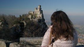 Kvinnan beundrar det Guaita tornet på monteringen Monte Titano i San Marino arkivfilmer