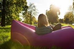 Kvinnan beundrar solnedgången på en uppblåsbar soffa Royaltyfri Foto