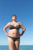 Kvinnan beväpnar akimbo posera mot havet Royaltyfri Fotografi