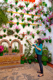 Kvinnan bevattnar blommorna på väggen, den Cordoba uteplatsfesten, Spa royaltyfri bild