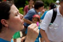 Kvinnan blåser bubblor, som folket lämnar fjärilsfestival Arkivfoto