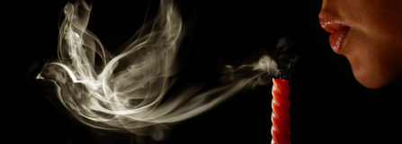 Kvinnan blåser ut en stearinljus arkivbilder