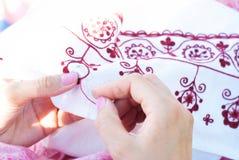 Kvinnan broderar den blom- prydnaden på linne Arkivbilder