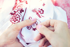 Kvinnan broderar den blom- prydnaden på linne Royaltyfri Foto