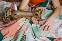Kvinnan broderar på symaskinen Royaltyfri Foto