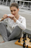 Kvinnan bryter ett svart schackstycke Arkivfoton