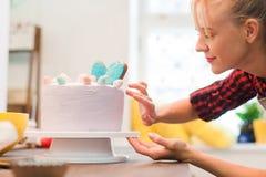 Kvinnan dekorerar den hemlagade kakan Kulinarisk affär royaltyfria foton